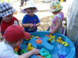 Toddlers at the sensory table outside
